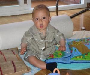 Puzzle de Bebé, contento y feliz, sentado en el suelo jugando con un libro