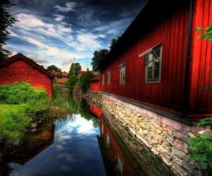 Puzzle de Casas de color rojo junto a un canal