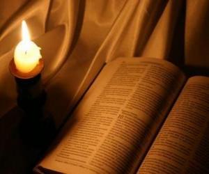 Puzzle de La Biblia y una vela encendida sobre el altar
