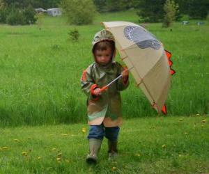 Puzzle de Niño con su paraguas y su chaqueta impermeable bajo la lluvia de primavera