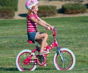 Puzzle de Niña montando una bicicleta por el parque en primavera