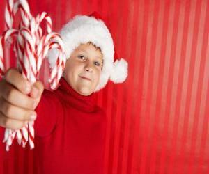 Puzzle de Niño con el gorro de Papá Noel y  bastoncitos de caramelo en la mano