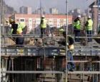 Vista general de una casa en construcción con diferentes operarios trabajando
