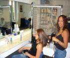 Peluquera peinando y secando el pelo a una clienta en el salón de belleza o peluquería