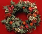 Corona de Navidad formada por hojas de acebo y frutas variadas