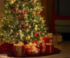 Árbol de Navidad adornado con bolas, lazos, una gran estrella y con los regalos debajo