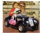 Niña en un coche clasico de juguete