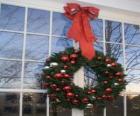 Gran corona de Navidad adornada con un gran lazo y bolas