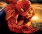 Spiderman con una joven en brazos colgados de una telaraña por el cielo de la ciudad