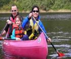 Familia, padre, madre, y hija, navegando y remando en una canoa, equipados con salvavidas