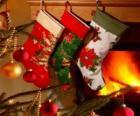 Calcetines navideños decorados y colgados en la pared de la chimenea