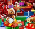 Osito de peluche con vestido de Papá Noel y con los regalos de Navidad