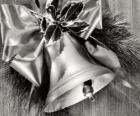 Campana navideña decorada con hojas de acebo y una cinta con un gran lazo
