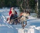 Papá Noel en su trineo con un reno sobre la nieve