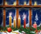 Velas de Navideñas encendidas delante de una ventana