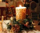 Vela encendida como centro de mesa adornada con ramitas de acebo y de abeto