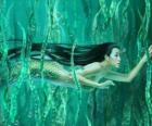Sirena nadando entre las algas
