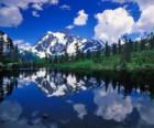 Un lago con el reflejo de la motaña en sus aguas
