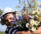 Un niño con el regalo para su madre, un gran ramo de flores
