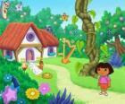 Dora, junto a una casa en el bosque
