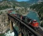 Tren de mercancias pasando por encima de un puente