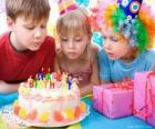 Niña en el momento de soplar las velas de su pastel de cumpleaños