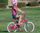 Niña montando una bicicleta por el parque en primavera