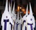 Nazarenos o penitentes durante una procesión de Semana Santa con capirote o cucurucho, túnica y capa