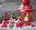 Lámpara de Navidad con vela encendida y adornos de acebo