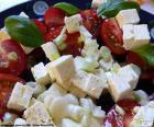 Una riquísima ensalada de queso feta, tomate, cebolla y canónigos