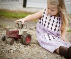Niña jugando con un tractor
