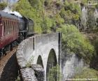 Un tren de vapor pasando por un antiguo viaducto de piedra