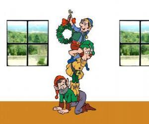 Puzzle de Tres duendes de Papá Noel colgando una corona navideña